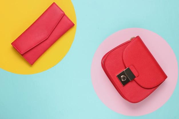 Rode leren tas en portemonnee op blauw met gekleurde cirkels.