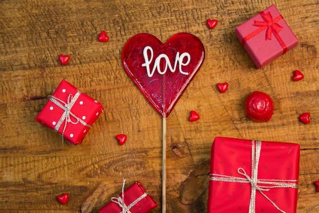 Rode liefde lollipop, cadeautjes en miniatuur glazen hartjes op houten tafel. valentijns decoratie
