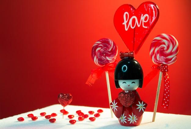 Rode liefde lollipop, cadeautjes en miniatuur glazen hartjes op tafel. valentijns decoratie