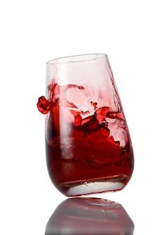 Rode limonade spatten in het glas geïsoleerd