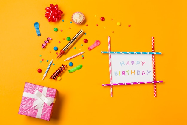 Rode lintboog; aalaw; edelstenen; streamers en hagelslag met gelukkige verjaardagskaart en geschenkdoos op gele achtergrond