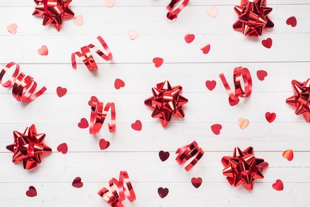Rode linten en strikken, confetti harten op een witte achtergrond. ruimte kopiëren plat leggen. wenskaart voor verjaardagsfeest, valentijnsdag van het huwelijk.