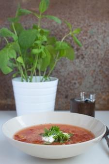 Rode linze-tomatensoep met zure room en munt