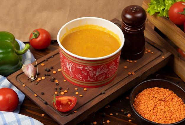 Rode linzensoep in wegwerpbeker kom geserveerd met groene groenten.