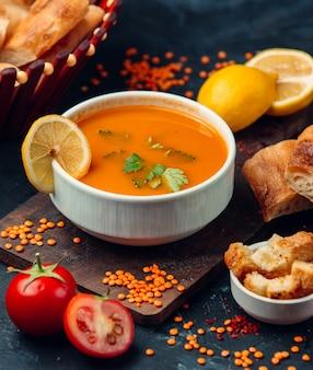 Rode linzensoep met een schijfje citroen en paneermeel