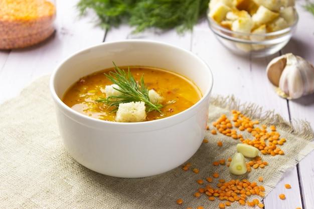 Rode linzensoep met ingrediënten op een lichte achtergrond. traditionele turkse of arabische pittige linzen- en groentesoep, gezond veganistisch eten. zijaanzicht