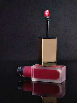 Rode lipgloss op een zwarte achtergrond met een borstel voor het aanbrengen van make-up