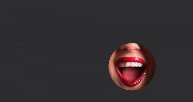 Rode lippen en glanzende glimlach door gat in donkergrijze document achtergrond