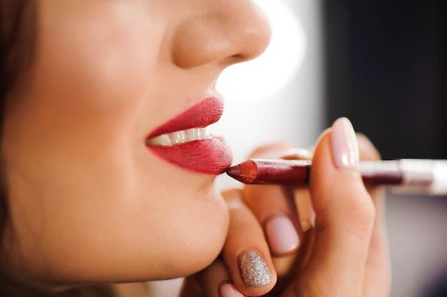 Rode lippenstift. close-up van vrouwengezicht met heldere rode matte lippenstift op volle lippen. schoonheidsschoonheidsmiddelen, make-upconcept. afbeelding met hoge resolutie.