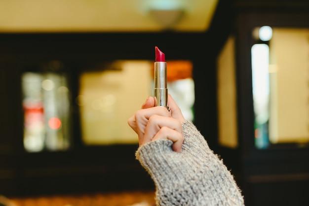 Rode lippenstift die door de hand van een vrouw wordt gehouden.