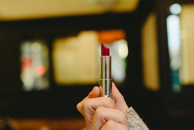 Rode lippenstift gehouden door de hand van een vrouw.