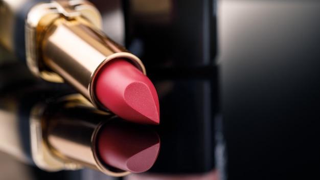 Rode lippenstift op donkere achtergrond met ruimte voor tekst