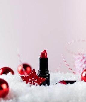 Rode lippenstiftbuis en kerstboomballen op kunstmatige sneeuwstapel