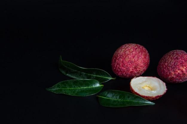 Rode litchifruit die in een mand wordt geplaatst.