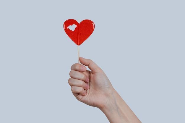 Rode lolly in de vorm van een hart in een vrouwelijke hand, op een grijze muur.