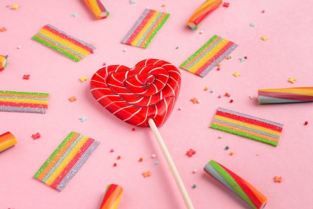 Rode lolly in de vorm van hart en kleurrijke snoepjes