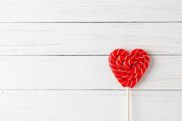 Rode lolly in vorm van hart op een witte houten achtergrond