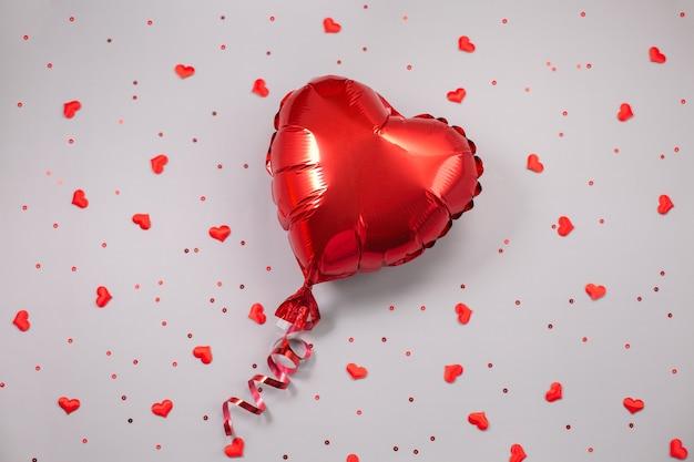 Rode luchtballon van hartvormige folie op feestelijke achtergrond.