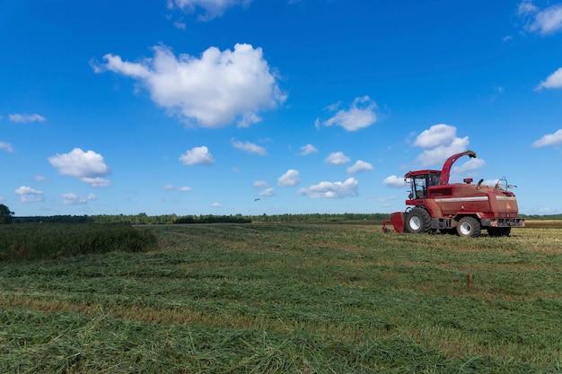 Rode maaimachine op een landelijk gebied. graan oogsten concept op een zonnige zomerdag, zijaanzicht.