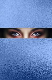 Rode make-upogen van een jong meisje in een spleet van blauw papier