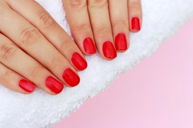 Rode manicure op witte handdoek, exemplaarruimte