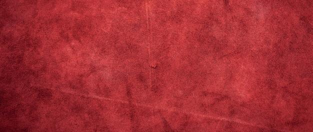 Rode matte achtergrond van suède stof, close-up. fluwelen textuur van naadloos leer.