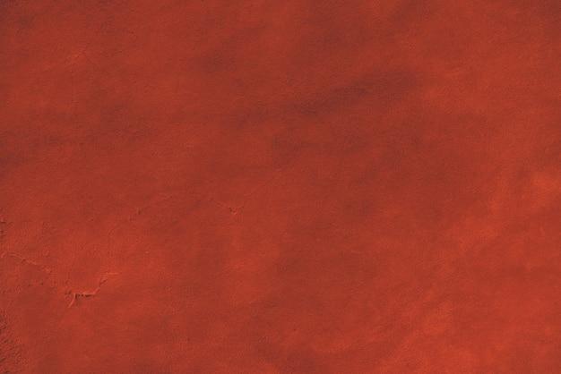 Rode matte achtergrond van suède stof. fluwelen textuur van naadloos leer. vilten materiaal. Premium Foto