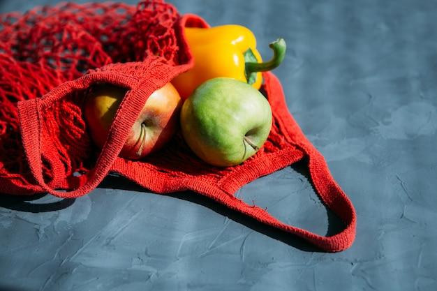 Rode mesh herbruikbare boodschappentas met groenten en fruit