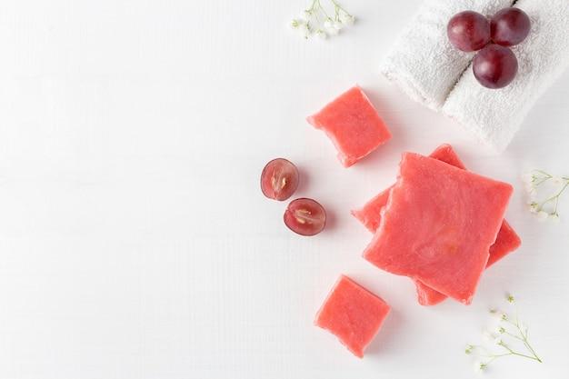 Rode met de hand gemaakte zeep en gesneden druiven dichtbij handdoeken en bloemen op wit hout