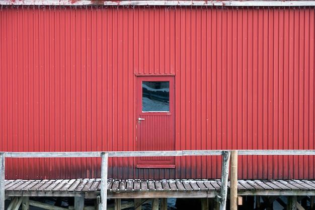 Rode metalen deur en muur van pakhuis op kustlijn in vissersdorp
