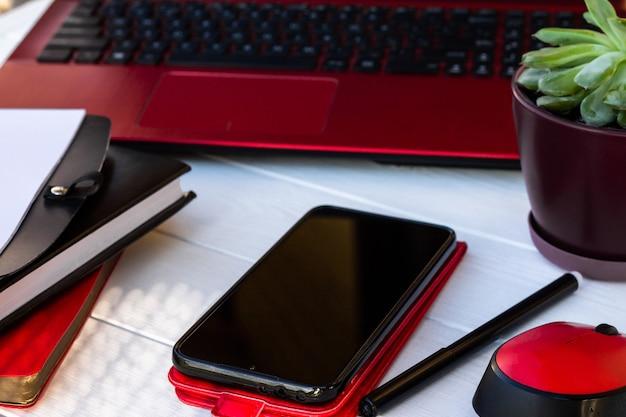 Rode mobiele telefoon, agenda en laptop op een witte houten achtergrond.