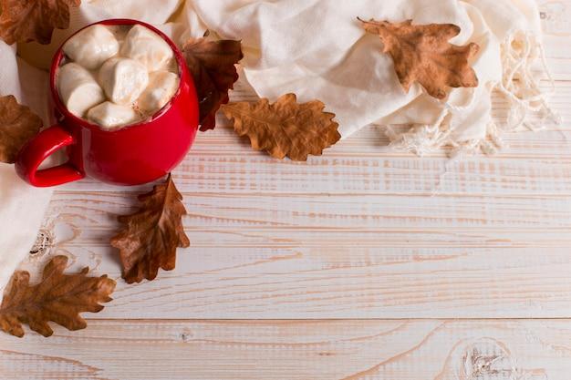 Rode mok met cacao en marshmallows, op een achtergrond van een sjaal en droge bladeren. herfststemming, een warm drankje.