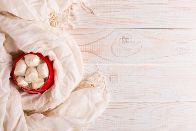 Rode mok met cacao en marshmallows op een witte tafel sjaal achtergrond. herfststemming, een warm drankje. copyspace.