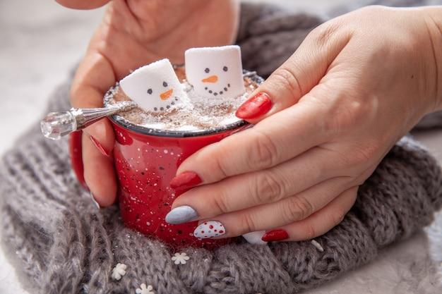 Rode mok met warme chocolademelk met gesmolten marshmallow sneeuwpop in handen van een vrouw