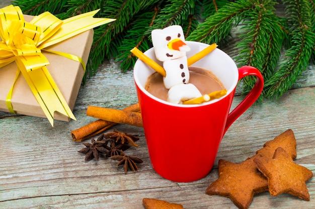 Rode mok met warme chocolademelk met gesmolten marshmallow sneeuwpop.