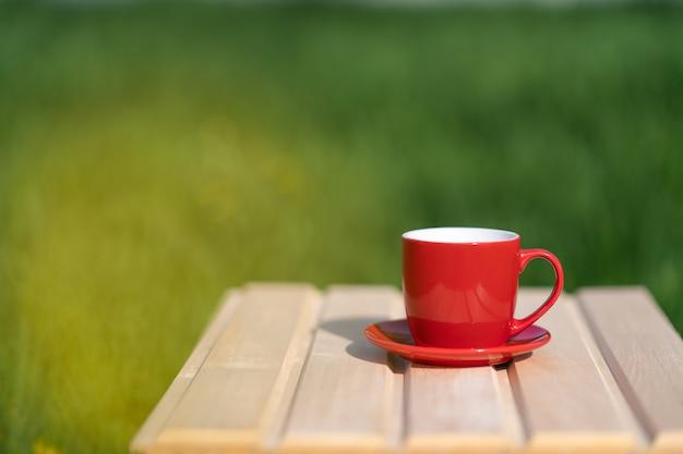 Rode mok op een houten tafel en groene achtergrond