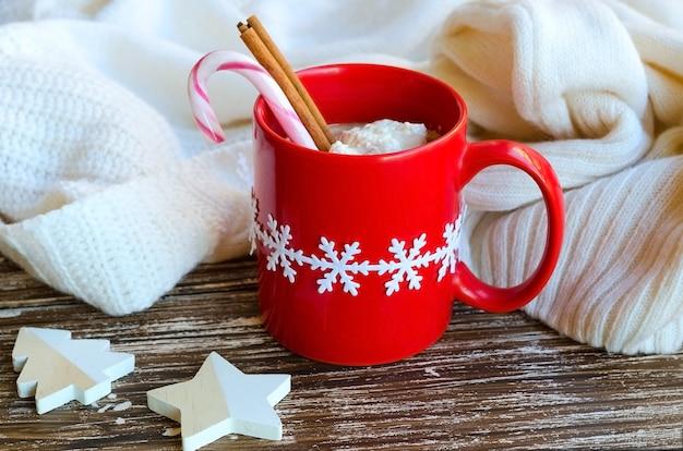 Rode mok warme chocolademelk met kaneelstokje en zuurstok, witte gezellige gebreide trui op de rug. heerlijke drank voor koud weer. wintertijd of kerstochtend concept.