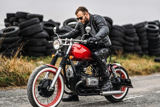 Rode motor met ruiter. man in een zwart lederen jas en broek begint een motorfiets.