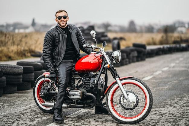 Rode motor met ruiter. man in een zwart lederen jas en broek staat zijwaarts in het midden van de weg.