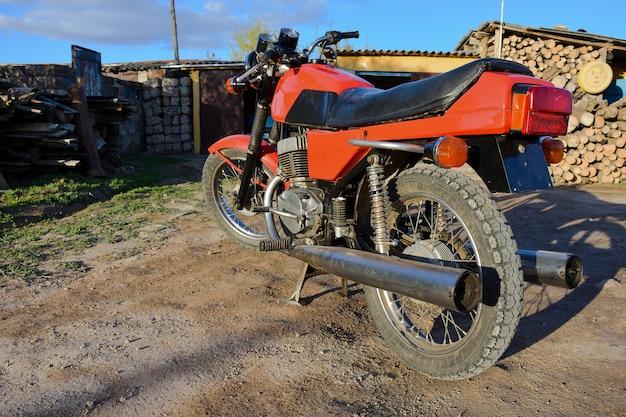 Rode motorfiets staat op de lege weg, vintage fiets
