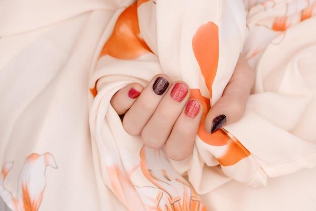 Rode nagel ontwerp. vrouwelijke hand met glitter manicure.