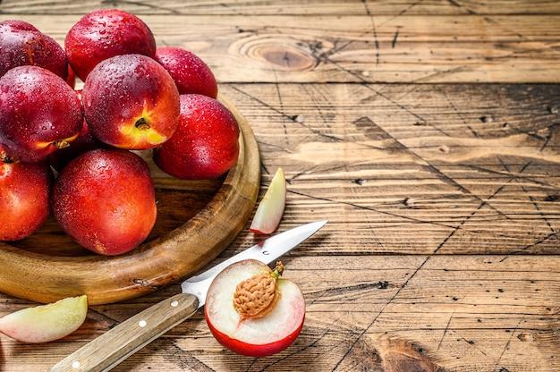 Rode nectarines op een houten dienblad en een halve nectarine.