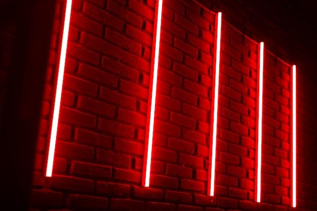Rode neonlijnen op bakstenen muur in nachtclub.