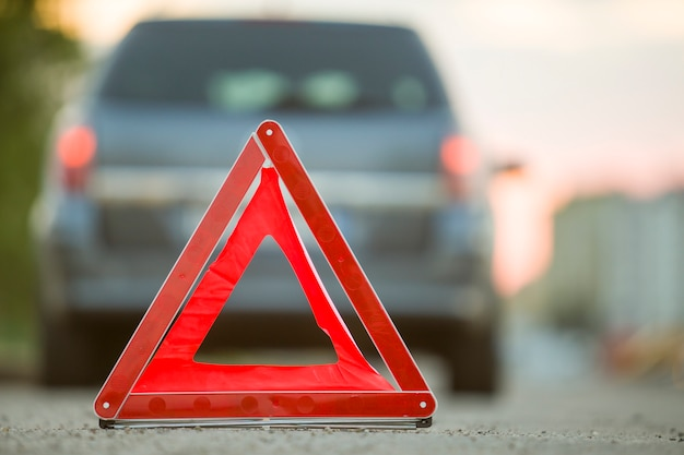 Rode nood driehoek stopbord en gebroken auto op een straat in de stad.