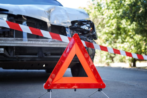 Rode nooddriehoek en rode waarschuwingspolitietape eerder vernietigde auto bij auto-ongeluk verkeersongeval op stadsweg. gebroken gebroken autokoplamp, gedeukte kap zonder bumper op grijs auto-ongeluk.