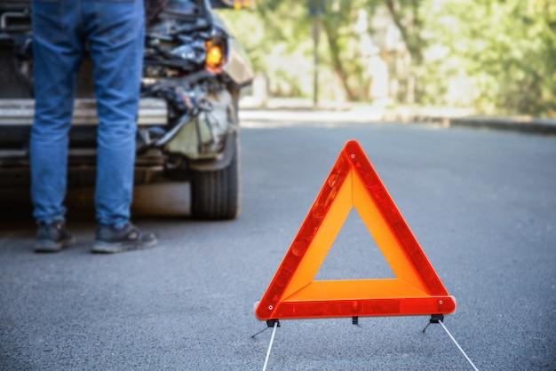 Rode noodstop driehoek eerder vernietigde auto in auto-ongeluk verkeersongeval op stadsweg. man loojing op smashed gebroken front auto auto-ongeluk.