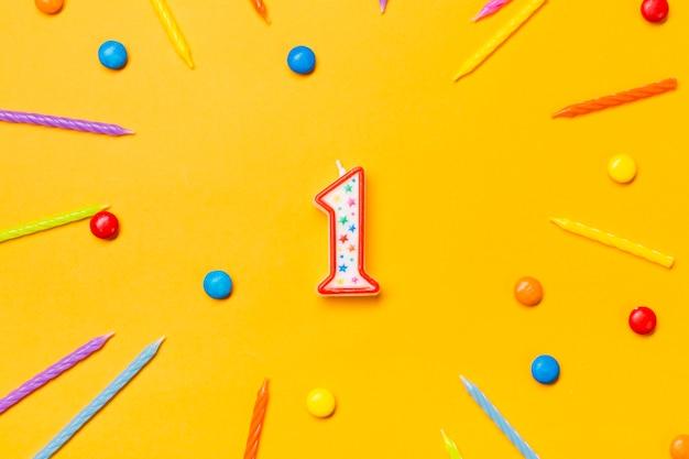 Rode nummer één kaars omringd met kleurrijke kaarsen en edelstenen op gele achtergrond