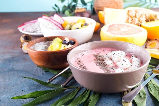 Rode of roze die smoothieaai kommen met verse pitaya en chiazaden worden bedekt op palmblad op steenachtergrond, exemplaarruimte