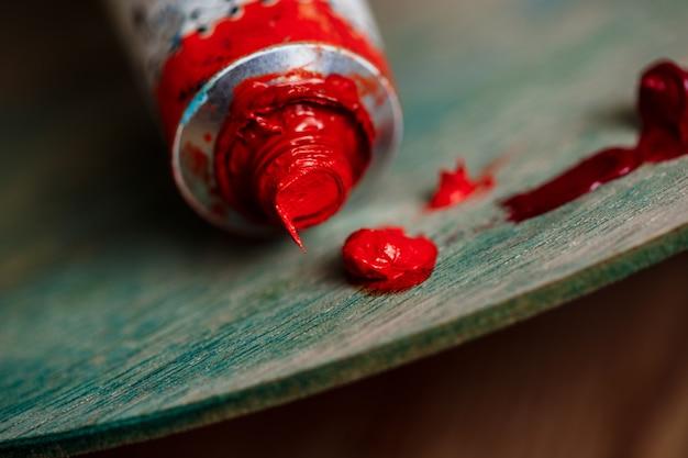 Rode olieverf op palet over houten muur