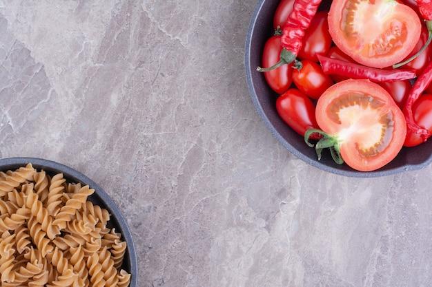 Rode ongekookte pasta's met kerstomaatjes op het marmeren oppervlak